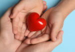 Closeup of woman and child holding heart on blue background, top view. Donation concept